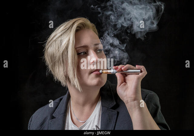 Woman looking on the side while smoking electronic cigarette - Stock Image