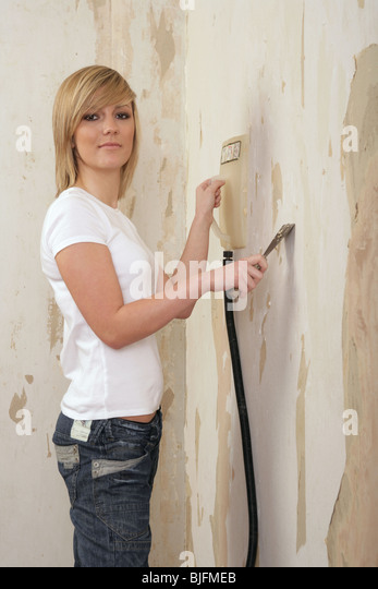 Pretty Blonde Girl Using A Steamer To Remove Wallpaper Stock Photo 28619539