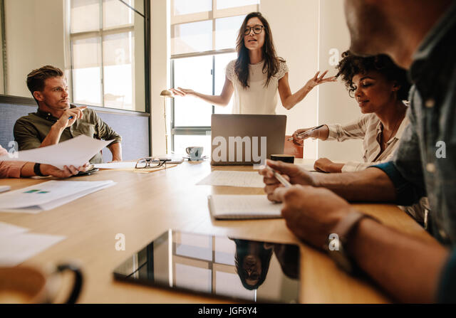Shot of young businesswoman giving presentation to her colleagues sitting around table in conference room. Multi - Stock Image