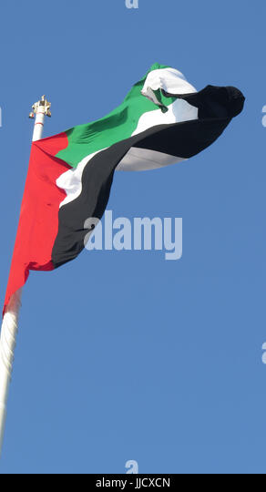 A huge flag of United Arab Emirates - UAE  fluttering in the wind, against clear blue skies. - Stock Image