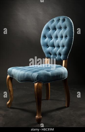 antique blue velvet chair near a dark room stock image
