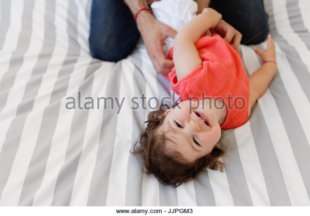 High angle view of man wearing jeans kneeling on bed with stripy duvet, playing with baby girl in red top. - Stock Image