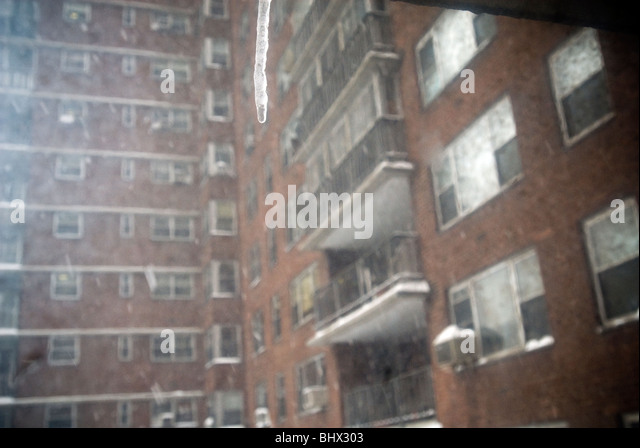 An Icicle Hangs From A Window As Snow Continues To Fall In New York