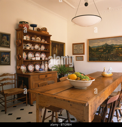 Bowl Of Fruit On Old Pine Table In Traditional Dining Room With Antique Dresser And Large