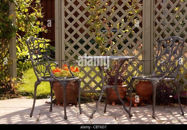 Sunlit Garden Patio With Trellis And Ornate Aluminium Garden Furniture,  England   Stock Image