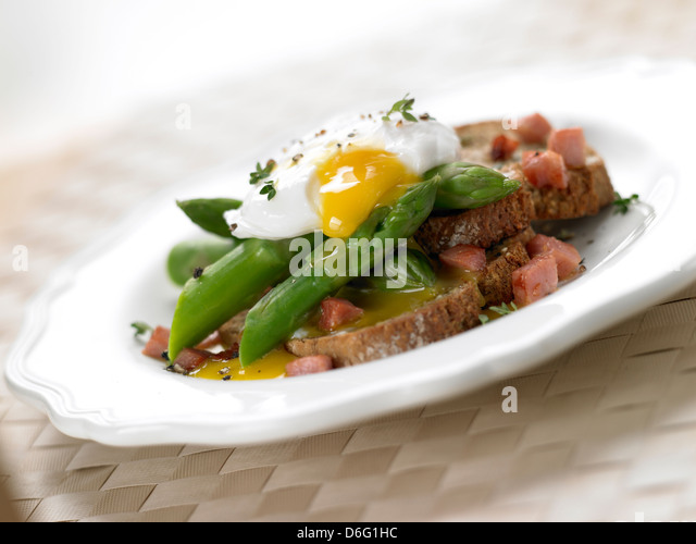 Asparagus with egg and Pancetta on toast / with recipe - Stock Image