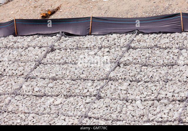 Gravel wire mesh bank revetment erosion control - Stock Image