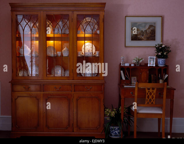 Desk And Chair Beside Glass Front Dresser With Interior Lighting In Eighties Dining Room
