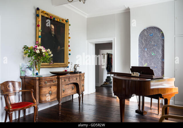 Large Portrait Above Mahogany Sideboard In Hall With Baby Grand Piano.    Stock Image