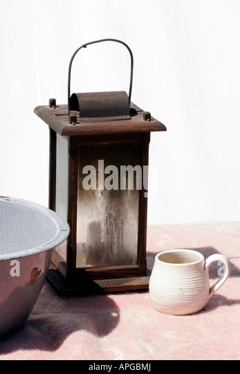 An Old Lantern With A Candle On A Table With An Antique Wash Basin And Clay