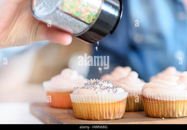 close up view of woman decorating cupcakes with confetti stock image