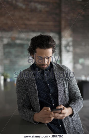 Creative businessman texting with smart phone in office - Stock Image