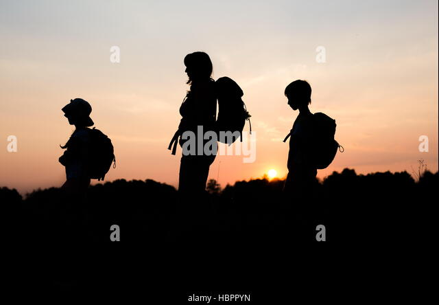 Silhouettes Of Family Hiking At Sunset Happy On Summer Vacation In Mountains Mom
