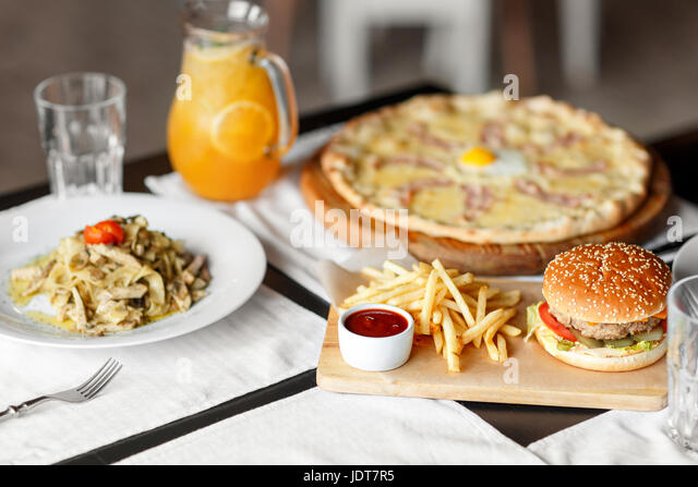 beautiful table of italian pasta, pizza, burger and drinks. selective soft focus - Stock Image