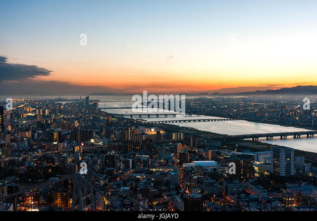 Japan, Osaka. Osaka and Kobe seen from top of Sky building. Yodogawa river with bridges at sunset with orange skies. - Stock Image