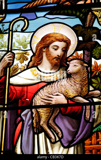 A Stained Glass Window Panel In Church Depicting Jesus As Shepherd Carrying Sheep