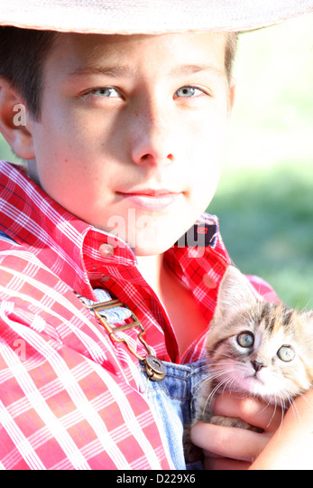 A farmer boy holding a small kitten Stock Photo - a-farmer-boy-holding-a-small-kitten-d229x6