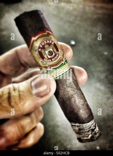 mans-hand-holding-lit-cigar-s02hcb.jpg
