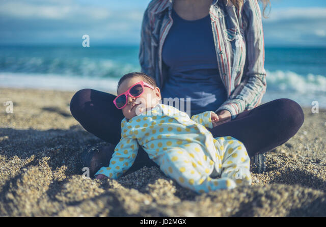 A cool baby is wearing sunglasses and is chilling out on the beach with his mother - Stock Image