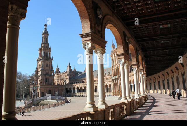 gallery and colonnade with an arch framing the tall south tower at sevilles plaza de espaa