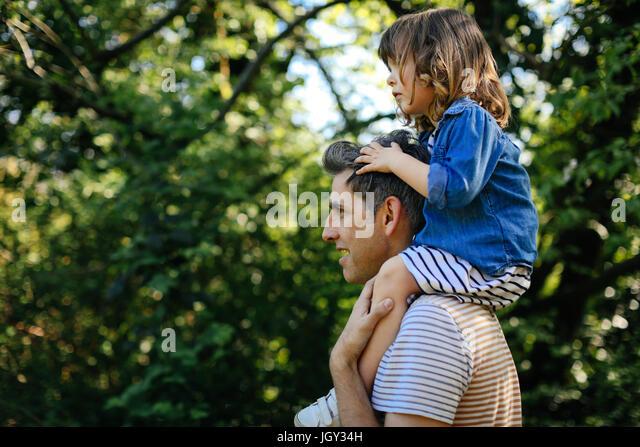 Father piggybacking little girl on nature walk - Stock Image