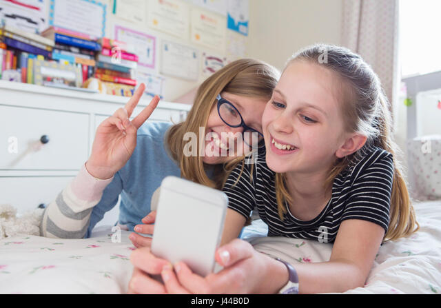 Two Young Girls Posing For Selfie In Bedroom - Stock Image