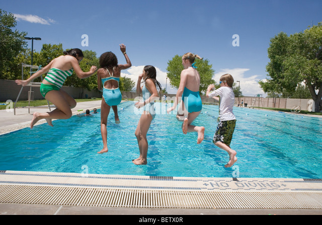 Kids Public Swimming Pool jumping into a swimming pool stock photos & jumping into a