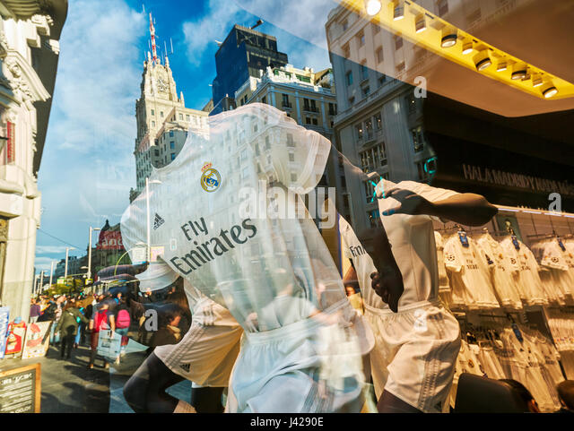 Mannequins and reflections at  Real Madrid Official Store  window shop at Gran V'a street. Madrid. Spain - Stock Image