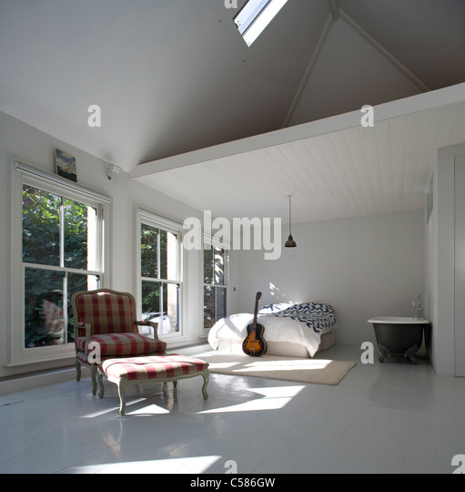 Double height bedroom bathroom with pitched ceiling - Stock Image