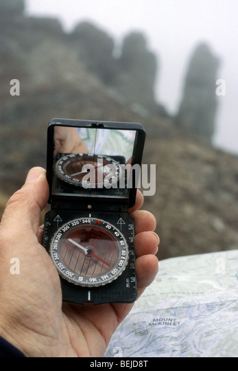 Hiker Reads Compass And Topographic Map For Orientation In The Fog In The Mountains Stock