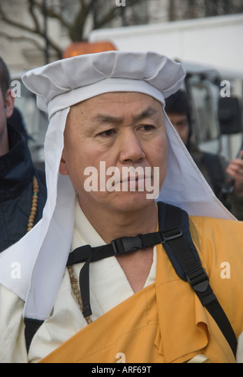 Burmese Buddhist monk in white and yellow robes at start of Burma Peace  March, London