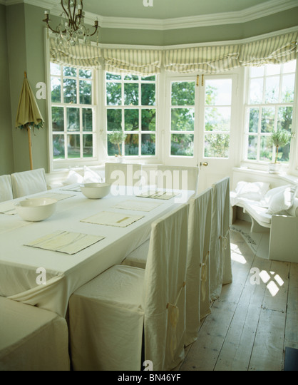 White Slip Covers On Chairs In Cream Country Dining Room With Linen Cloth Table
