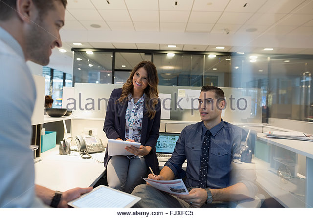 Business People With Paperwork Meeting In Office Cubicle