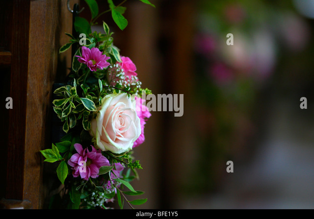 Wedding flowers on church pew stock photos wedding flowers on flowers on the end of a church pew as wedding decoration stock image junglespirit Image collections
