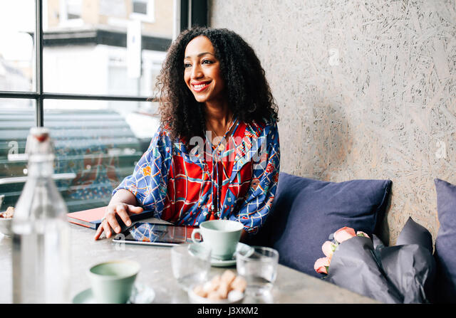 Mid adult woman on cafe window seat - Stock Image