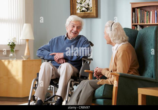 Senior Couple In Care Home Man Wheelchair