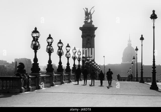 People walks on the historical Bridge Alexandre III ( Pont Alexandre III ) in Paris. Black and White image. - Stock Image