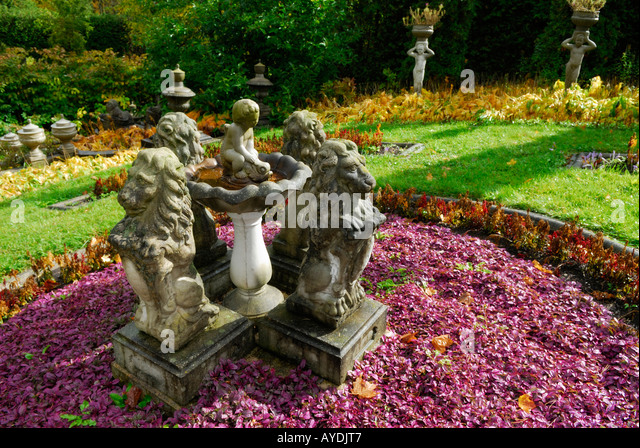Purple Adjuga Plant In Sun In An Autumn Garden With Lion And Cherub Statues  In Sunshine