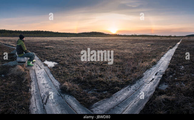 Hiker sitting in swamp with nice sunset landscape - Stock Image
