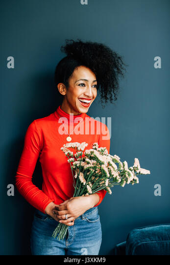 Portrait of happy florist holding cut flowers - Stock Image