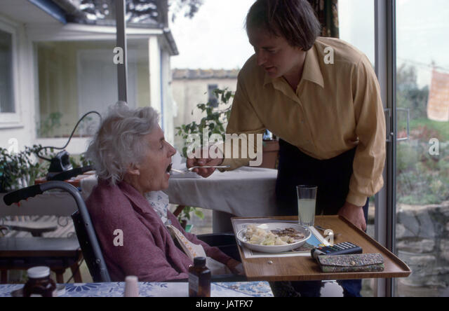 Carer assisting woman with Motor Neurone Disease - Stock Image