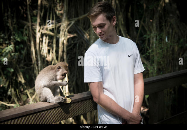 young-man-watches-a-monkey-eating-gn3bgb