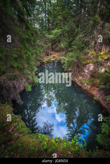 Old and historical mine full with greenish jade color water in middle of forest. This mine is over 500 hundred years - Stock Image