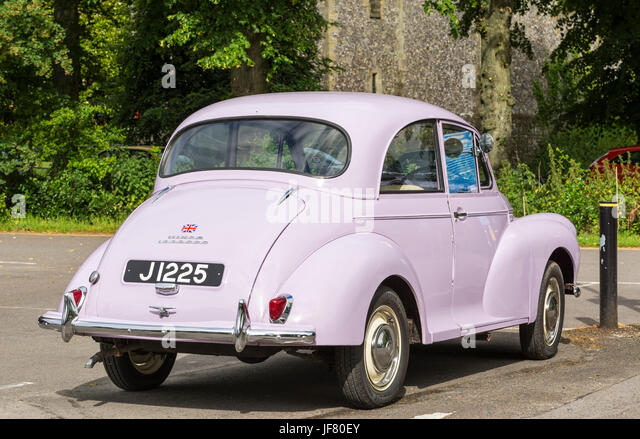 Morris Minor 1000000 car called 'Millie' in pink, parked in a car park. - Stock Image