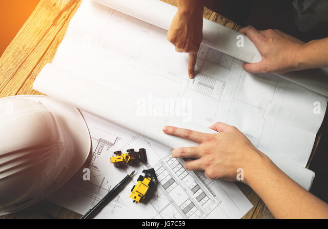 Creative architect projecting on the big drawings in the dark loft office with dark and retro style - Stock Image