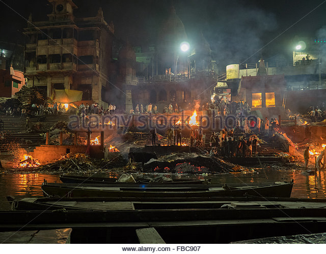 indians burning the funeral pyre on the river ganges People look at the funeral pyre that night the ceremony of the cremation of manikarnika ghat on the banks of the ganges river in varanasi, india foto von dmitrii melnikov auf mostphotos.