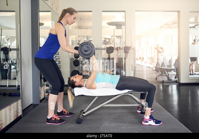 Young woman working out with barbell weights on a bench in the gym with the assistance of her personal trainer in - Stock Image