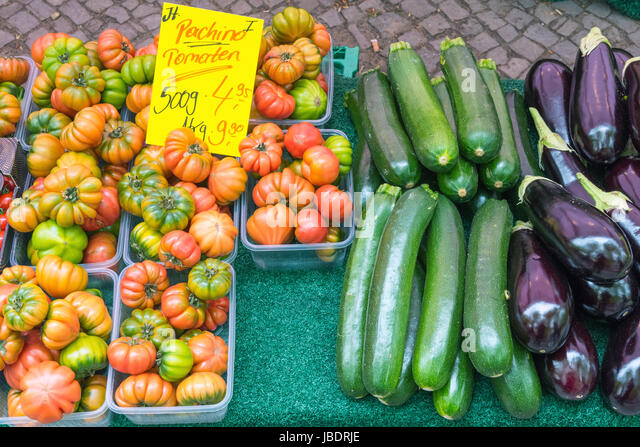 Tomatoes, eggplant and zucchini for sale at a market - Stock Image