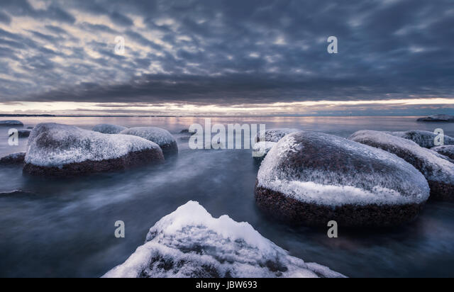 Scenic landscape with sea and sunset at winter time in rocky coastline - Stock Image