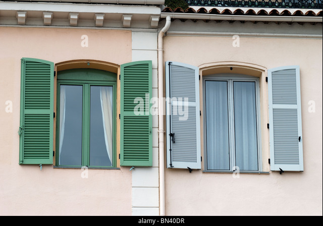 Windows with two different colored frames and shutters to apartment  building in Cannes. Cote d